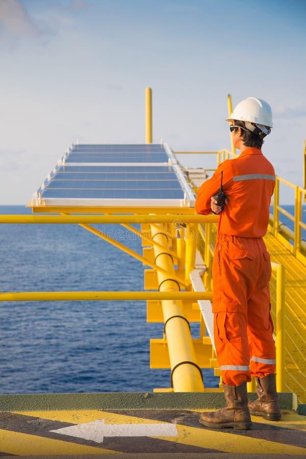 Técnico eléctrico y del instrumento en la plataforma del telecontrol del manantial del petróleo y gas fotografía de archivo
