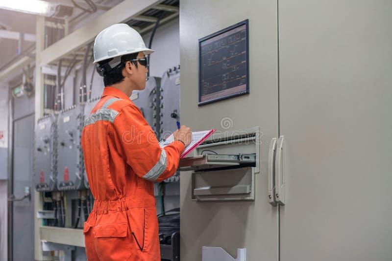 Técnico eléctrico y del instrumento que comprueba sistemas de control eléctricos de proceso del petróleo y gas en sitio eléctrico imagenes de archivo