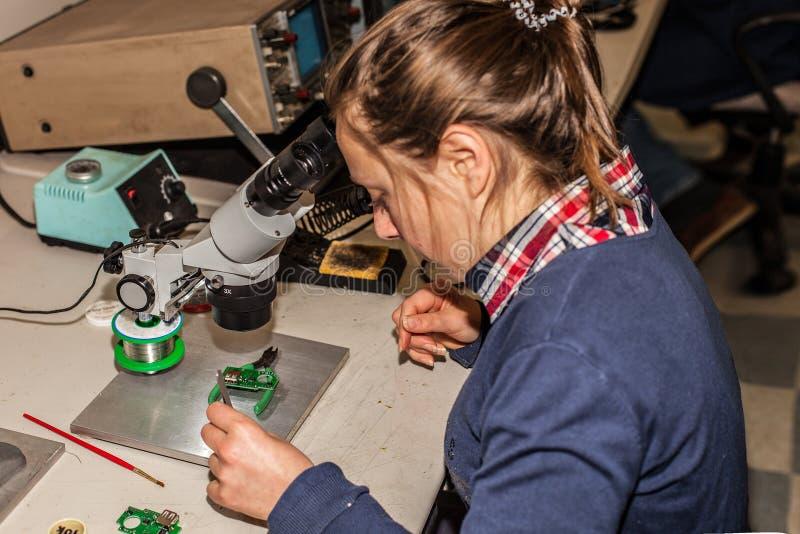 Técnico electrónico de sexo femenino joven en el trabajo foto de archivo