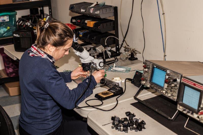 Técnico electrónico de sexo femenino joven en el trabajo imagen de archivo