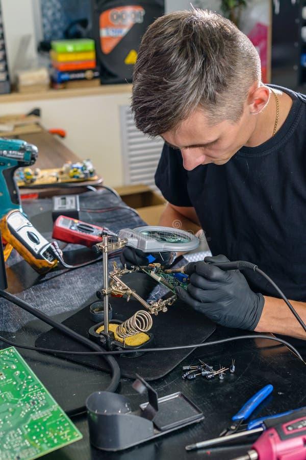 Técnico electrónico profesional que repara el equipo en un centro de servicio foto de archivo libre de regalías