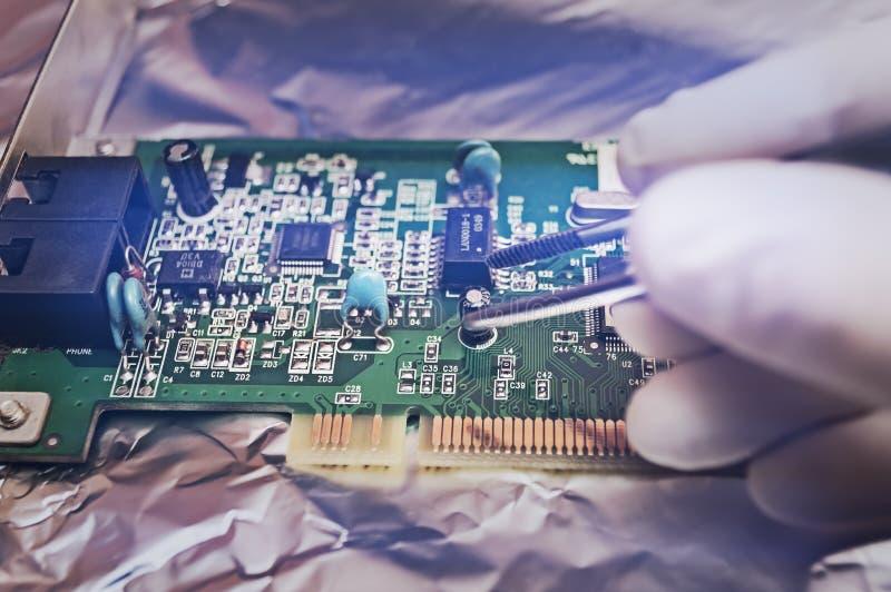 Técnico electrónico que repara el hardware en el laboratorio fotos de archivo