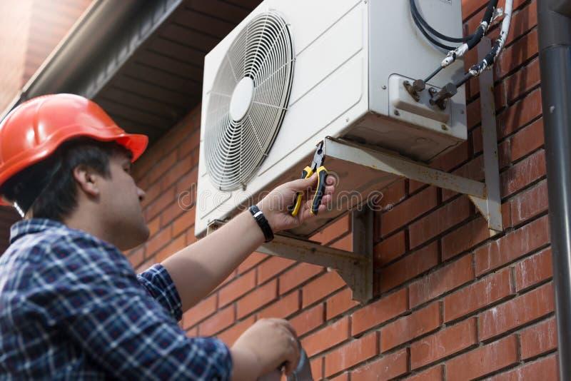 Técnico en el casco de protección que conecta la unidad de aire acondicionado al aire libre imagenes de archivo