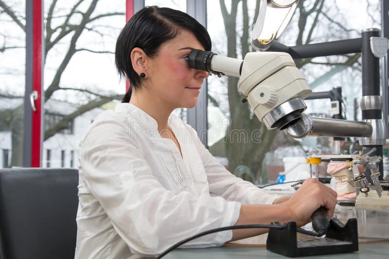 Técnico en un laboratorio o un taller dental que trabaja debajo de un microscopio imagenes de archivo