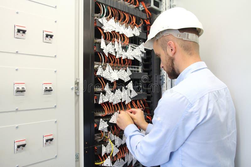 Técnico en la caja de las comunicaciones que conecta fibras optas imágenes de archivo libres de regalías
