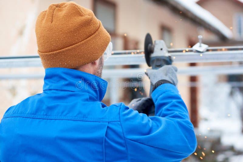 Técnico masculino no metal azul do corte do terno com a roda do corte para instalar os painéis solares imagem de stock royalty free