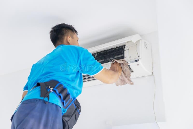 Técnico masculino que limpa o condicionador de ar com um pano fotos de stock