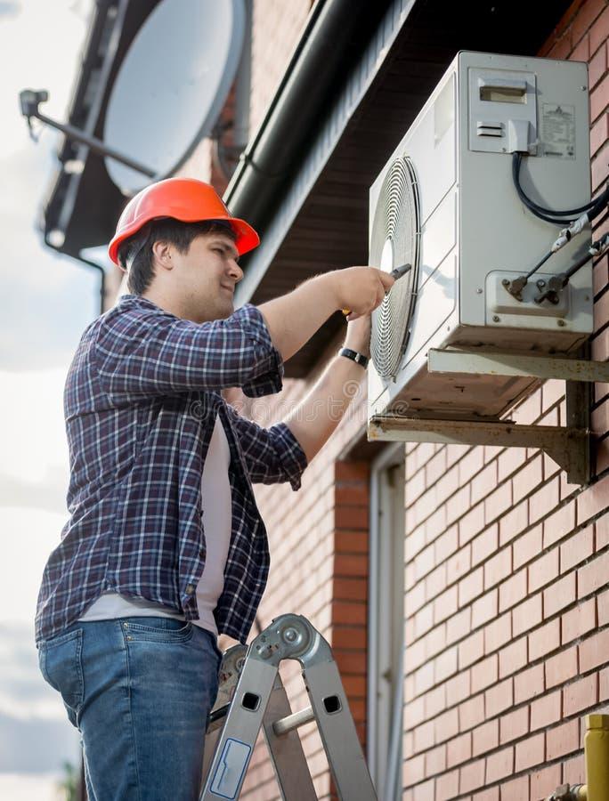 Técnico masculino que repara o sistema de condicionamento de ar exterior imagens de stock