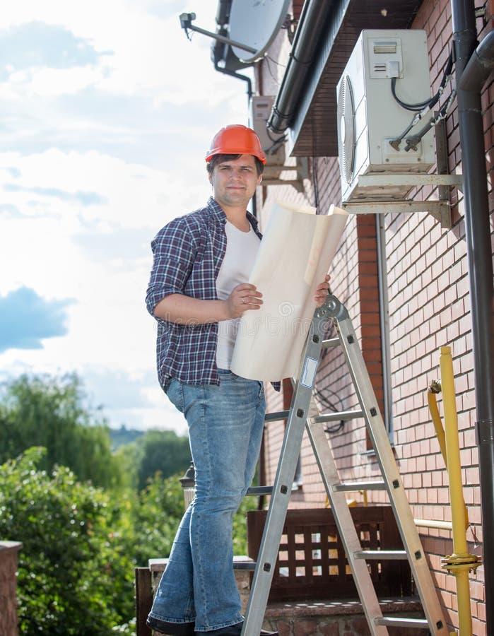 Técnico masculino que verifica o sistema de condicionamento de ar com o instructio fotografia de stock