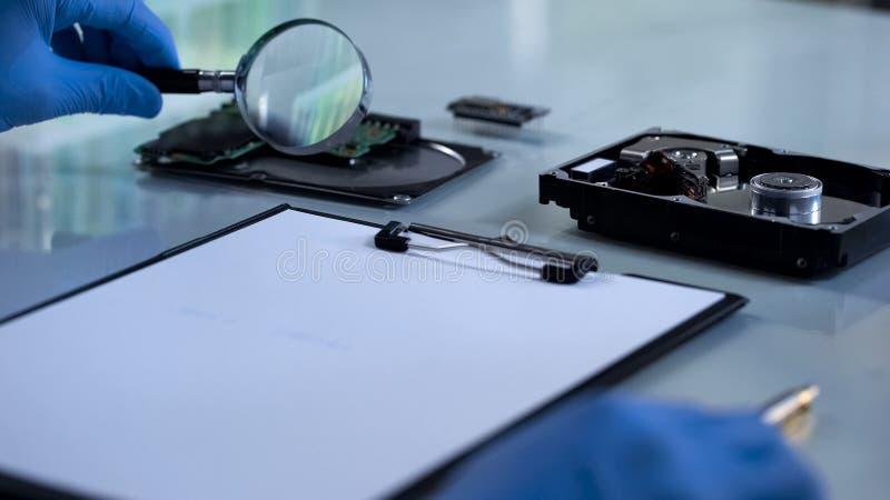 Técnico nas luvas que olham o microcircuito através da lupa, ciência imagem de stock