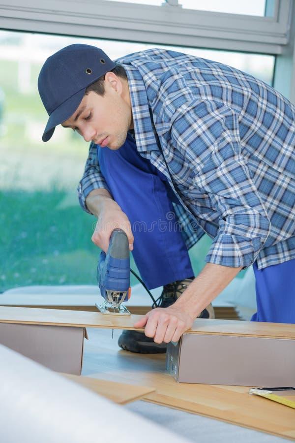 Técnico novo que instala o assoalho no canteiro de obras fotografia de stock