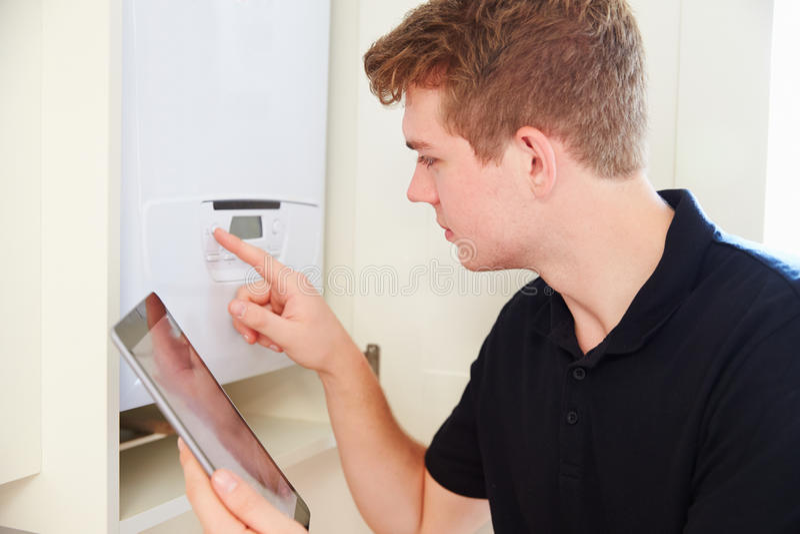 Técnico novo que presta serviços de manutenção a uma caldeira, usando o tablet pc imagens de stock