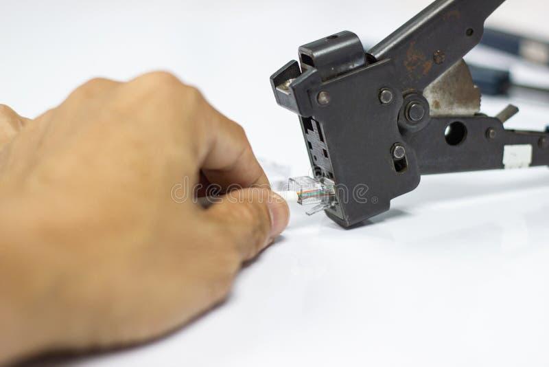 Técnico para instalar um conector RJ45 em um cabo do remendo da rede CAT5 Ethernet imagens de stock royalty free