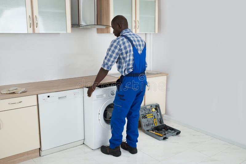 Técnico Pulling Washing Machine en cocina foto de archivo libre de regalías