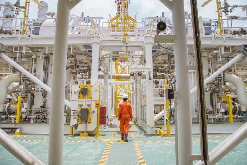 Técnico que anda com o processo a pouca distância do mar do petróleo e gás para verificar a condição do equipamento na plataforma imagem de stock royalty free