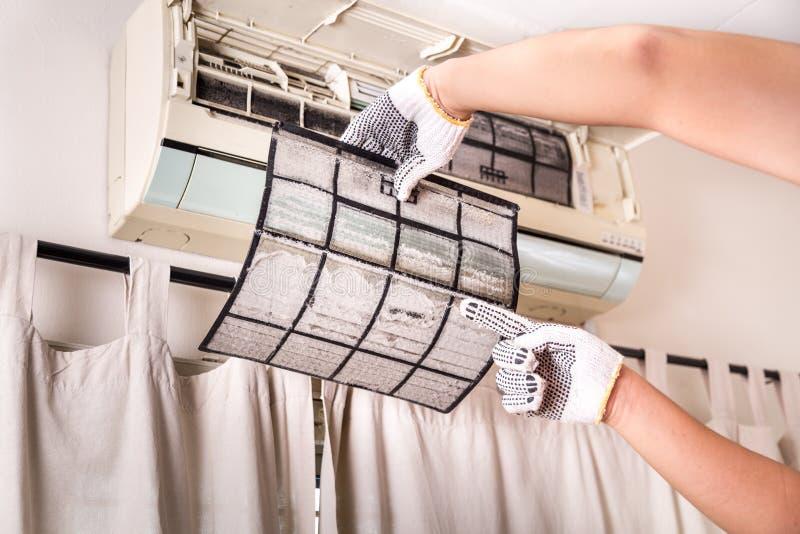 Técnico que aponta ao filtro do condicionador de ar completamente do du prendido fotografia de stock