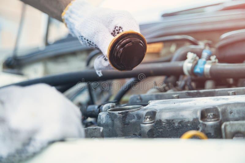 Técnico que comprueba el nivel de aceite en motor de coche imagenes de archivo