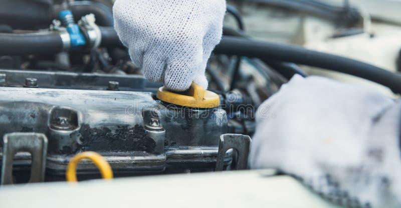 Técnico que comprueba el nivel de aceite en motor de coche foto de archivo