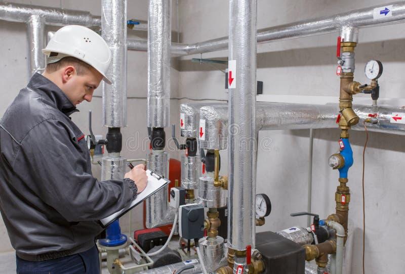 Técnico que examina el sistema de calefacción en sitio de caldera fotos de archivo