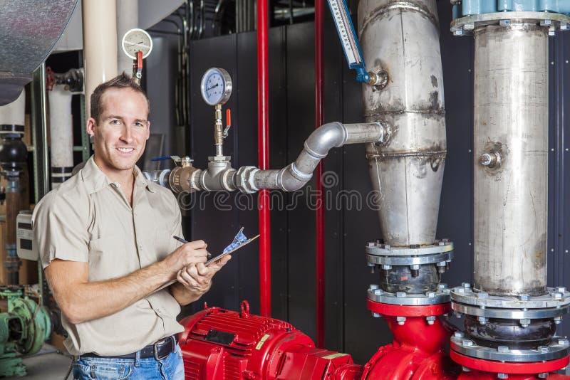 Técnico que inspeciona o sistema de aquecimento na caldeira foto de stock