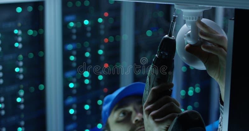 Técnico que instala a câmara de segurança foto de stock