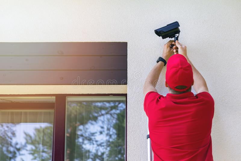 Técnico que instala a câmara de vigilância exterior da segurança na parede de exterior da casa imagem de stock