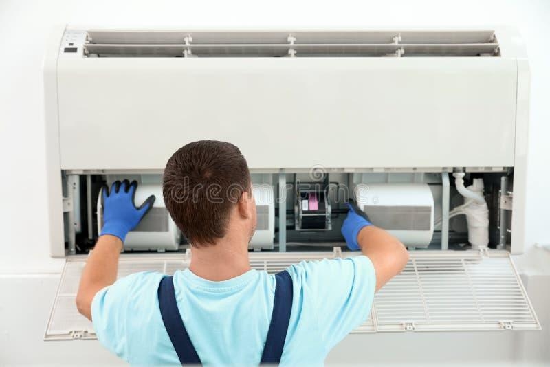 Técnico que instala e que verifica o condicionador de ar imagens de stock