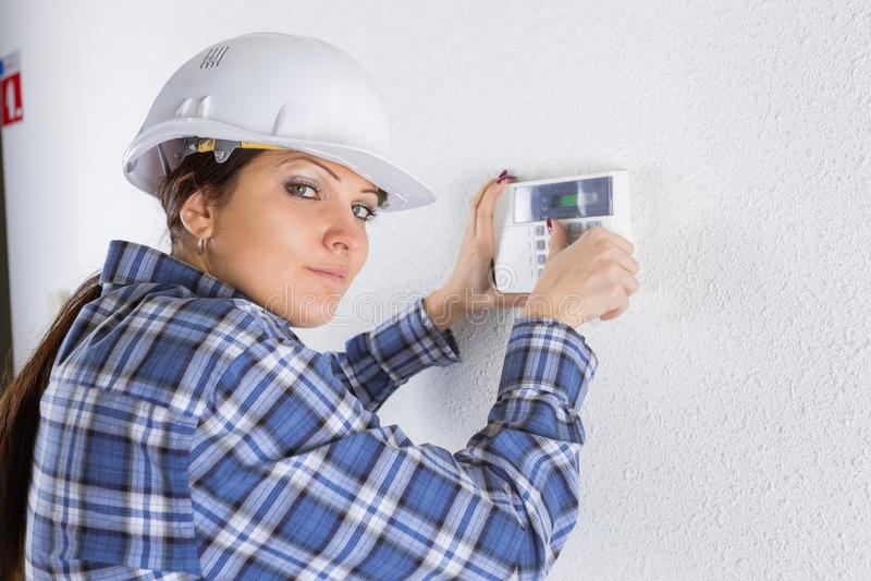 Técnico que instala el sensor de la puerta del sistema de seguridad fotografía de archivo