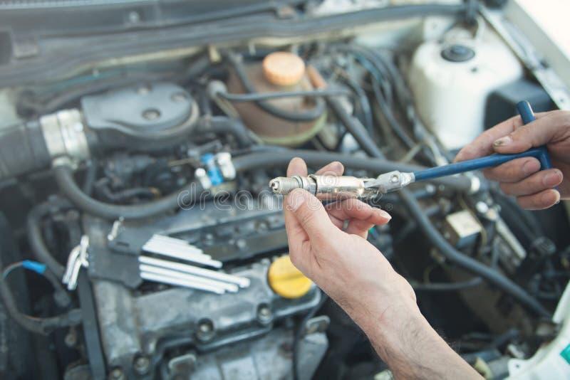 Técnico que instala la nueva vela en motor de coche fotos de archivo