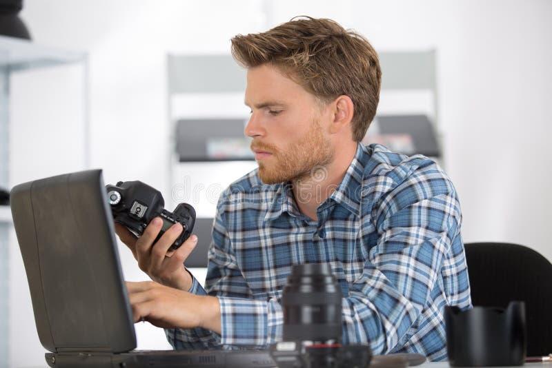 Técnico que lleva a cabo el componente y que usa el ordenador portátil imágenes de archivo libres de regalías