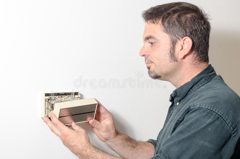 Técnico que remove a tampa do termostato imagem de stock