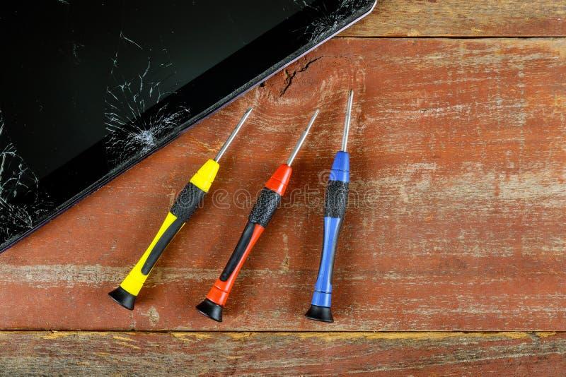 Técnico que repara dentro de la tableta por el destornillador en la tecnología de reparación electrónica del teléfono móvil imagen de archivo libre de regalías