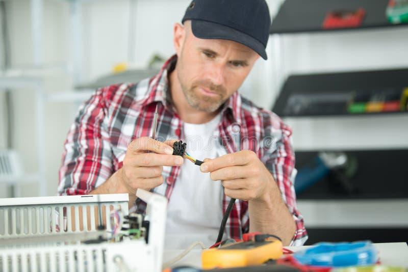 Técnico que repara el radiador en taller imagen de archivo libre de regalías
