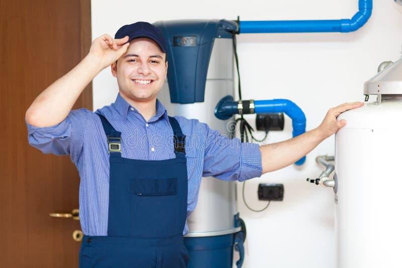 Técnico que repara um calefator de água quente imagens de stock