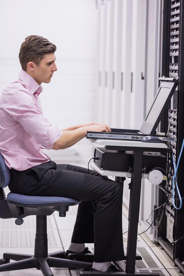 Técnico que se sienta en silla de eslabón giratorio usando el ordenador portátil para diagnosticar los servidores imagenes de archivo