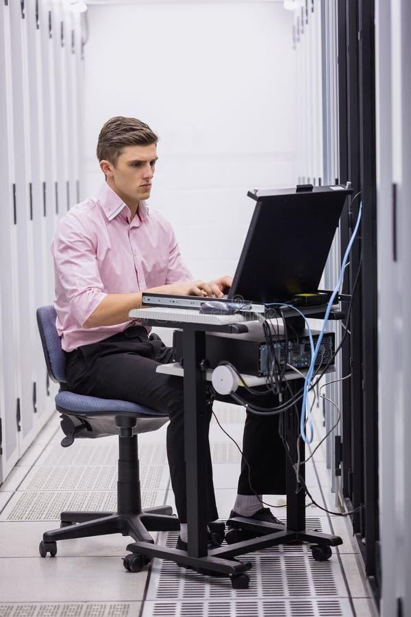 Técnico que se sienta en silla de eslabón giratorio usando el ordenador portátil para diagnosticar los servidores fotografía de archivo