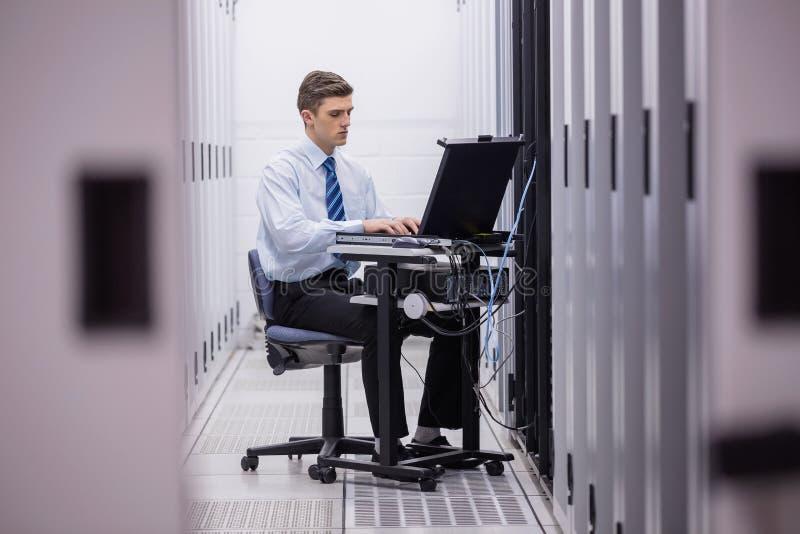 Técnico que se sienta en silla de eslabón giratorio usando el ordenador portátil para diagnosticar los servidores fotos de archivo libres de regalías