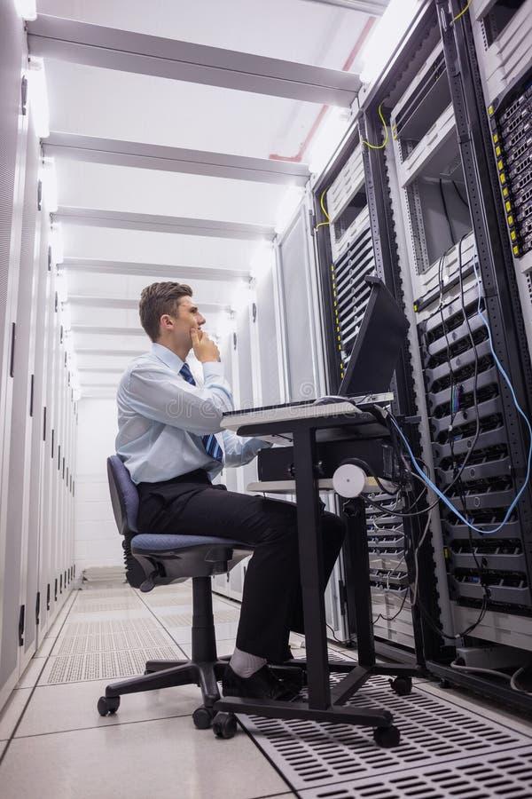 Técnico que se sienta en silla de eslabón giratorio usando el ordenador portátil para diagnosticar los servidores fotografía de archivo libre de regalías