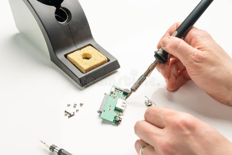 Técnico que solda um componente eletrônico com um ferro de solda fotos de stock royalty free