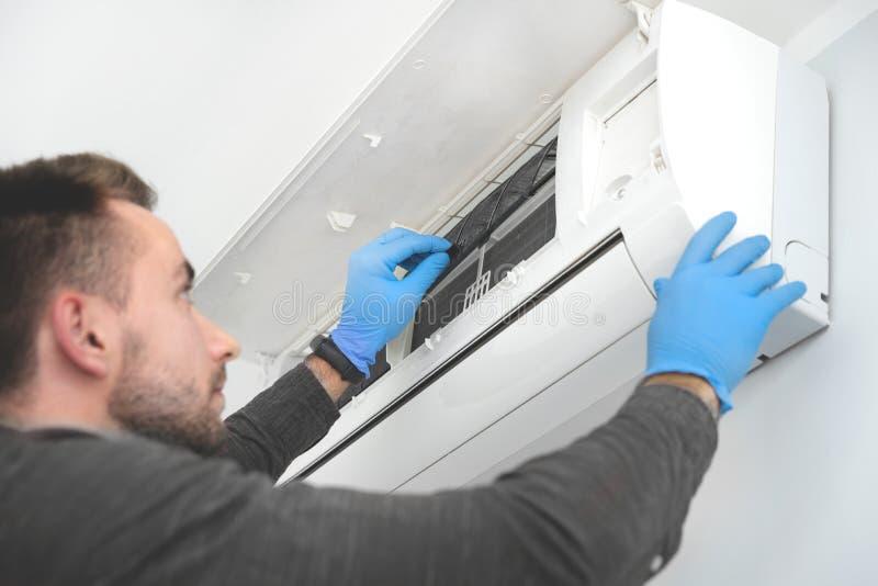 Técnico que substituye el filtro en aire acondicionado imagen de archivo