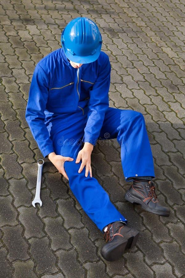 Técnico que sufre de dolor de la rodilla en la calle imagen de archivo libre de regalías