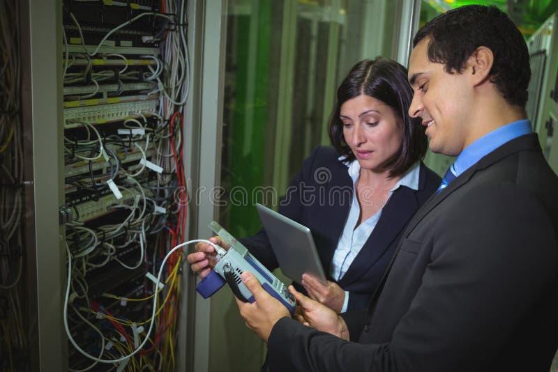 Técnico que trabalha no computador pessoal ao analisar os técnicos do servidor que usam o cabo digital analy foto de stock