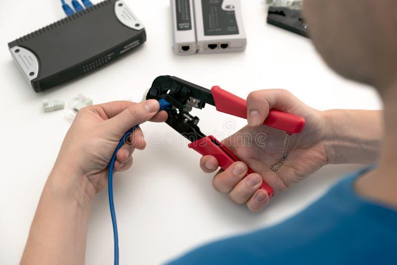 Técnico que usa el arrugador del cable de la red fotografía de archivo