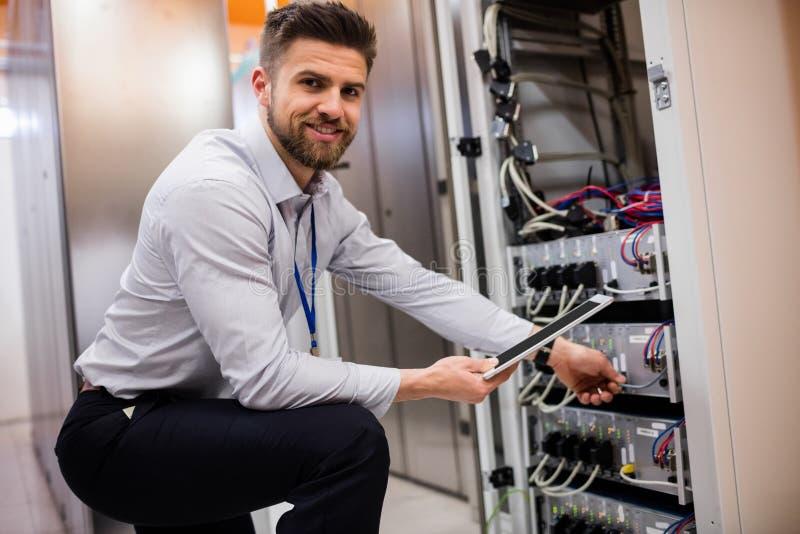 Técnico que usa la tableta digital mientras que analiza el servidor imagen de archivo