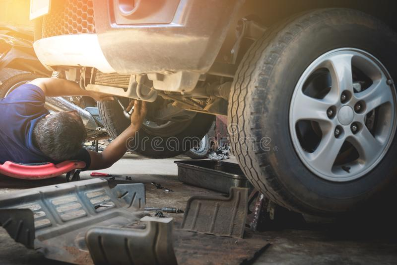 Técnico que verifica o motor do carro Auto mecânico que verifica o en do carro imagens de stock royalty free