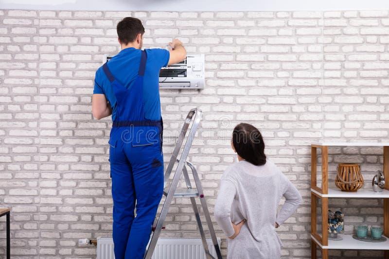 T?cnico Repairing Air Conditioner com mult?metro digital fotografia de stock royalty free
