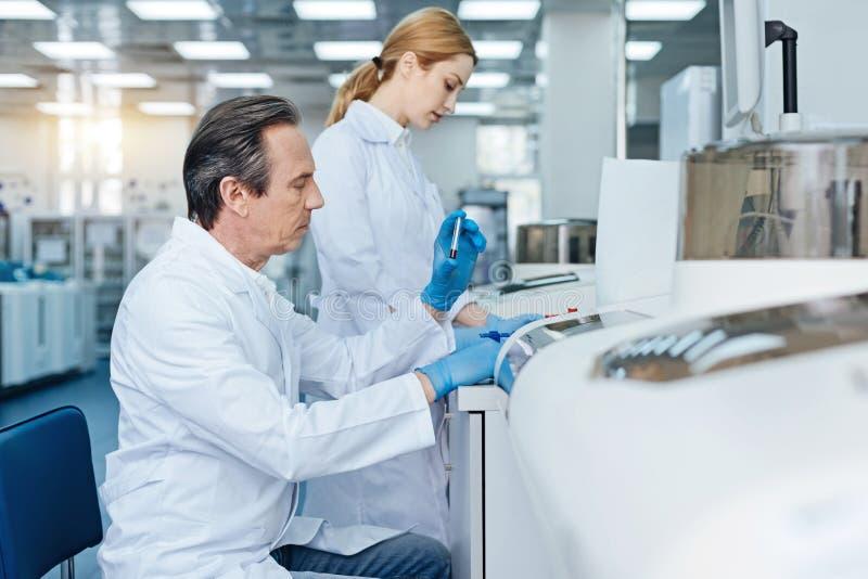 Técnico sério que faz a análise do sangue imagem de stock