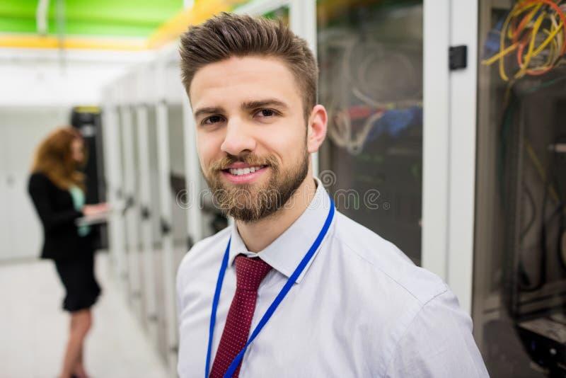 Técnico sonriente que se coloca en un cuarto del servidor imagen de archivo