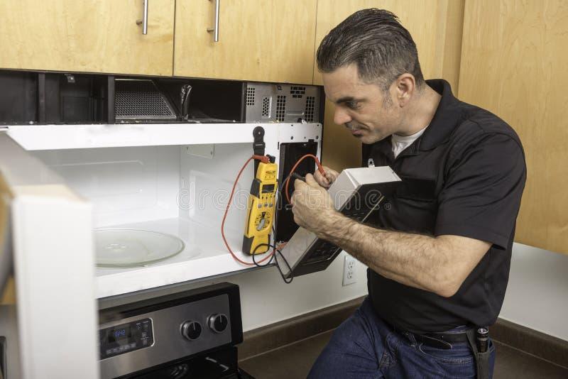 Técnico Troubleshooting Microwave do dispositivo fotos de stock