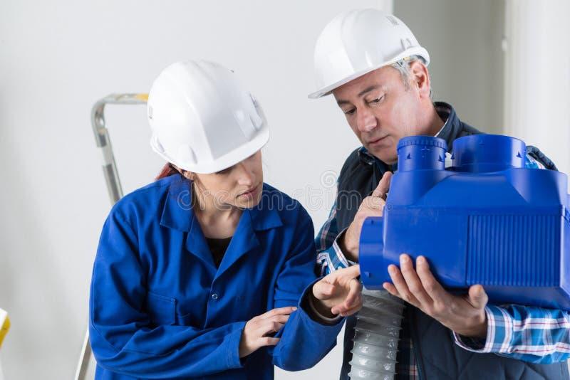 Técnico y aprendiz que trabajan en los tubos de la ventilación fotos de archivo